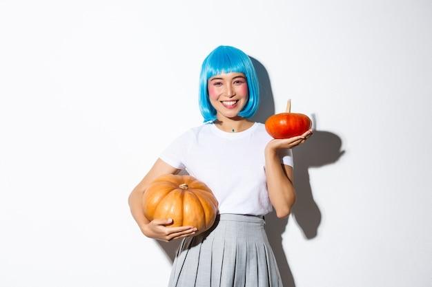 Bild des entzückenden asiatischen mädchens in der blauen perücke, halloween feiern, große und kleine kürbisse zeigend und glücklich lächelnd stehend.