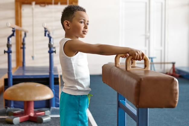 Bild des entzückenden glücklichen dunkelhäutigen atheltischen kindes in den blauen shorts und im weißen t-shirt, die im fitnessstudio aufwerfen