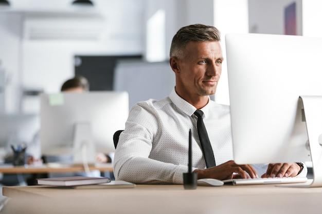 Bild des erfolgreichen angestelltenmanns 30, der weißes hemd und krawatte trägt, die am schreibtisch im büro sitzen und am computer arbeiten