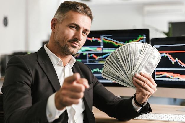 Bild des erfreuten geschäftsmanns der 30er jahre, der anzug hält, der geldfächer hält, während im büro mit grafiken und diagrammen auf computer arbeitet