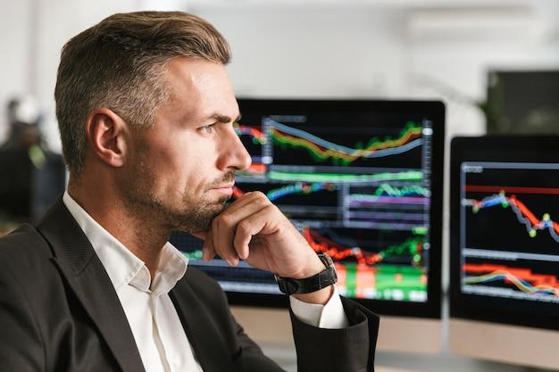 Bild des ernsthaften geschäftsmanns 30s tragen anzug, der im büro am computer mit grafiken und diagrammen am bildschirm arbeitet