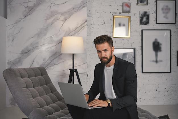 Bild des ernsthaften gutaussehenden erfahrenen jungen kaukasischen männlichen profis, der in seiner stilvollen modernen wohnung arbeitet, auf der couch in formeller kleidung sitzt, tastaturen mit offenem tragbarem computer