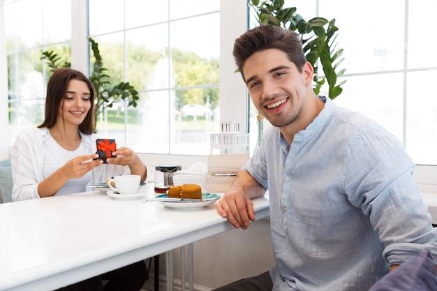 Bild des erstaunlichen jungen liebenden paares, das im café sitzt, essen desserts und trinkt tee. mann schaut, während seine freundin ihr geschenk ansieht.