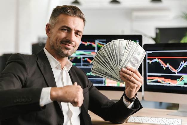 Bild des erwachsenen geschäftsmannes der 30er jahre, der anzug hält, der geldfächer hält, während im büro mit grafiken und diagrammen auf computer arbeitet