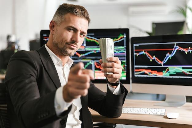Bild des erwachsenen geschäftsmannes der 30er jahre, der anzug hält packung geld während der arbeit im büro mit grafiken und diagrammen auf computer