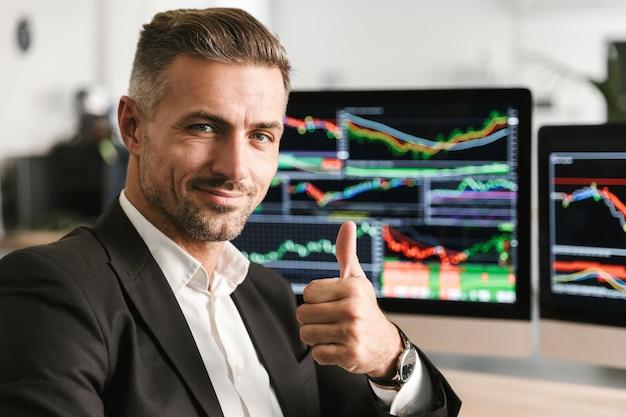 Bild des europäischen geschäftsmannes 30s tragen anzug, der im büro am computer mit grafiken und diagrammen am bildschirm arbeitet