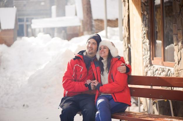 Bild des familienpaares in einer winterkleidung, die auf einer holzbank sitzt.