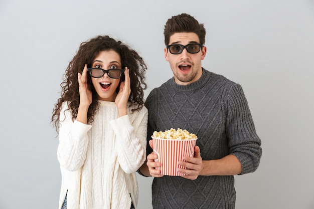 Bild des freudigen mannes und der frau, die 3d-schutzbrillen tragen, die eimer mit popcorn halten, lokalisiert über graue wand