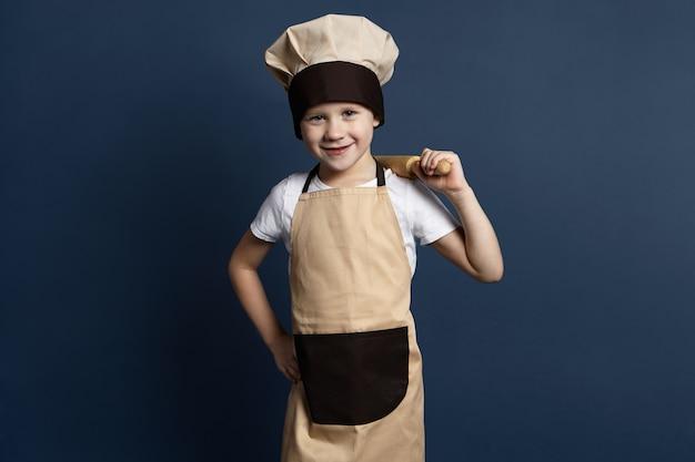Bild des fröhlichen blauäugigen 7-jährigen jungenkochs in der kochuniform, der nudelholz auf seiner schulter hält, froh ist, während teig für lebkuchenplätzchen knetet, kamera mit glücklichem lächeln betrachtend