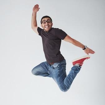 Bild des fröhlichen jungen mannes, der lässig gekleidet über weiß springt