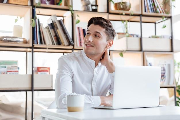 Bild des fröhlichen mannes im weißen hemd mit laptop-computer gekleidet. coworking. sieh zur seite.