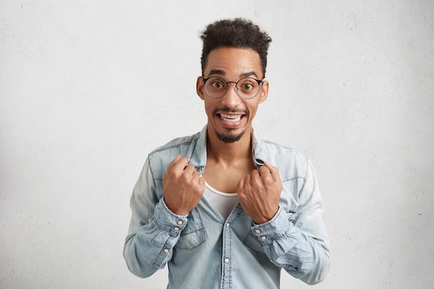 Bild des fröhlichen mannes mit ovalem gesicht, trägt runde brille, reißt hemd ab,