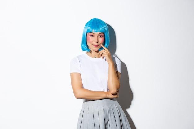 Bild des gerissenen lächelnden asiatischen mädchens in der blauen parteiperücke, die hinterhältig in die kamera schaut, haben eine idee, stehend.