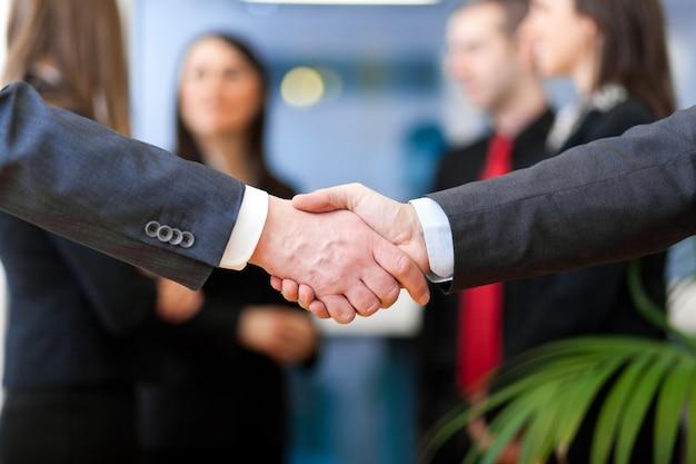 Bild des geschäftspartnern händedrucks auf unterzeichnendem vertrag