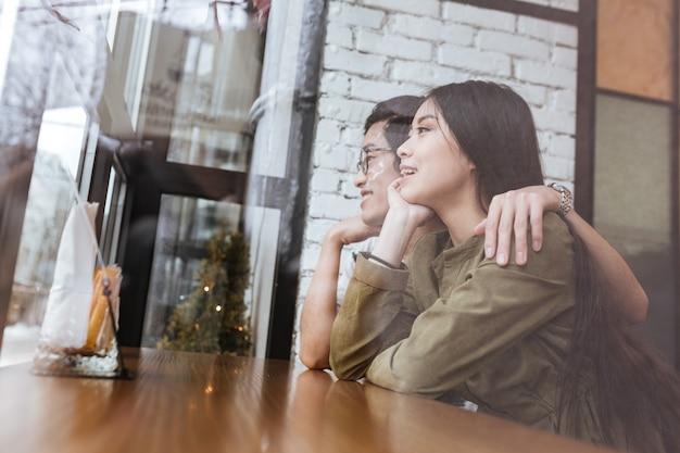 Bild des glücklichen asiatischen jungen liebespaares am café. zur seite schauen.