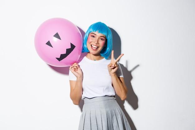 Bild des glücklichen asiatischen mädchens, das halloween in der blauen animeperücke feiert, rosa ballon mit gruseligem gesicht haltend und friedensgeste zeigt.