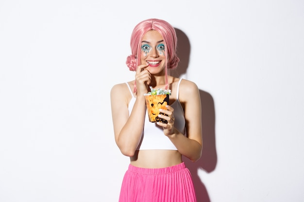 Bild des glücklichen attraktiven mädchens mit rosa perücke und hellem make-up, das süßes oder saures geht, halloween feiert, süßigkeiten zeigt und lächelt, stehend.
