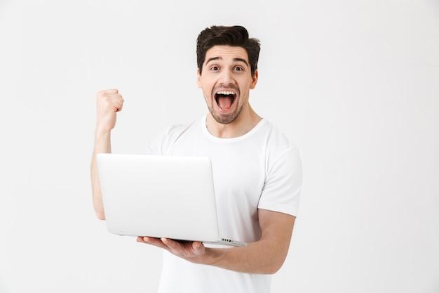 Bild des glücklichen aufgeregten jungen mannes, der lokalisiert über weißer wand mit laptop-computer posiert, machen siegergeste.