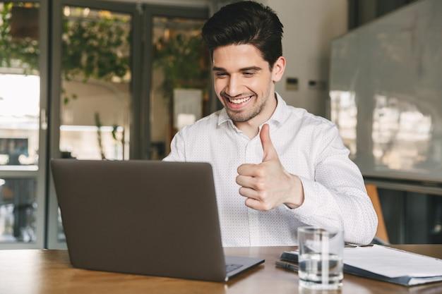 Bild des glücklichen büro-kerls 30s, der lachendes weißes hemd trägt und daumen oben am laptop zeigt, während videokonferenz oder anruf