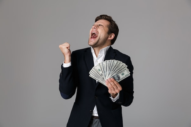 Bild des glücklichen geschäftsmannes 30s im anzug lächelnd und hält fan des geldes in dollarbanknoten, lokalisiert über graue wand