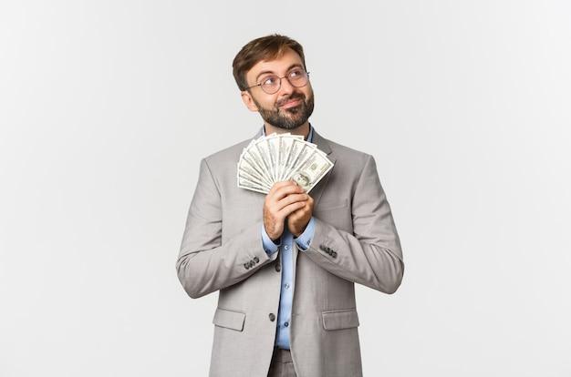 Bild des glücklichen geschäftsmannes mit bart, der grauen anzug und brille trägt
