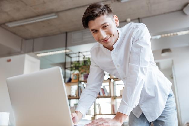 Bild des glücklichen jungen mannes, der im weißen hemd unter verwendung des laptopcomputers gekleidet wird. coworking. schauen sie in die kamera.