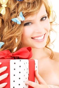 Bild des glücklichen mädchens mit geschenk und schmetterlingen über weiß