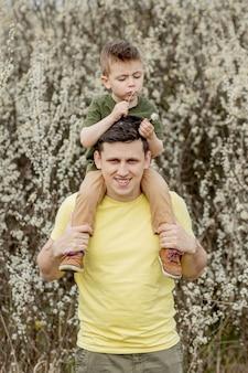 Bild des glücklichen mannes, der seinen sohn hält, während spaß hat.