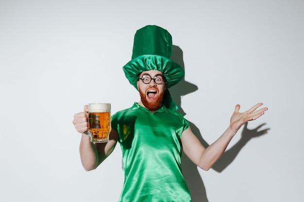 Bild des glücklichen mannes im st.patriks kostüm, das bier hält