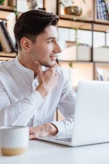 Bild des glücklichen mannes im weißen hemd mit laptop-computer gekleidet. coworking. sieh zur seite.