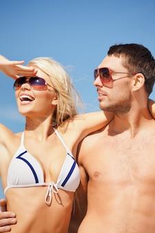 Bild des glücklichen paares mit sonnenbrille am strand.