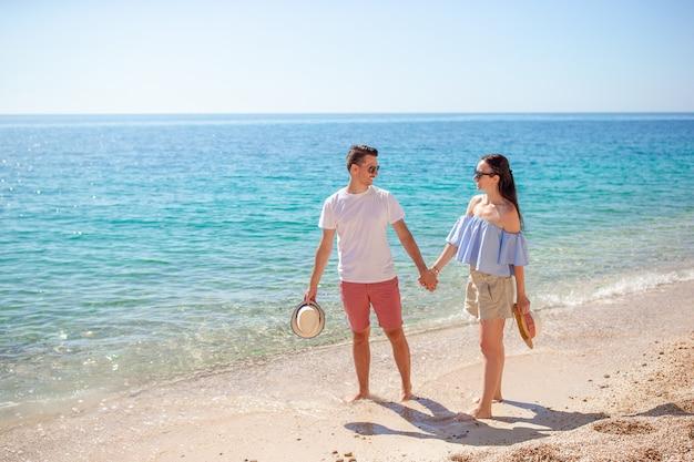 Bild des glücklichen paars in der sonnenbrille auf dem strand
