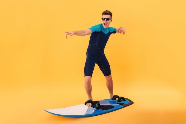 Bild des glücklichen surfers im neoprenanzug und in der sonnenbrille, die surfbrett wie auf welle verwenden