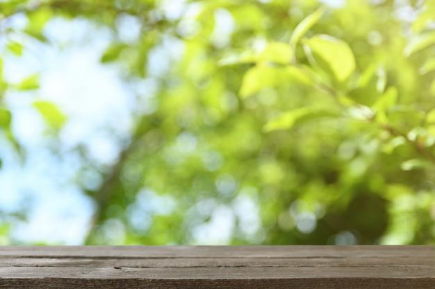 Bild des grauen holztisches vor abstraktem unscharfem hintergrund der grünen blätter und der bäume