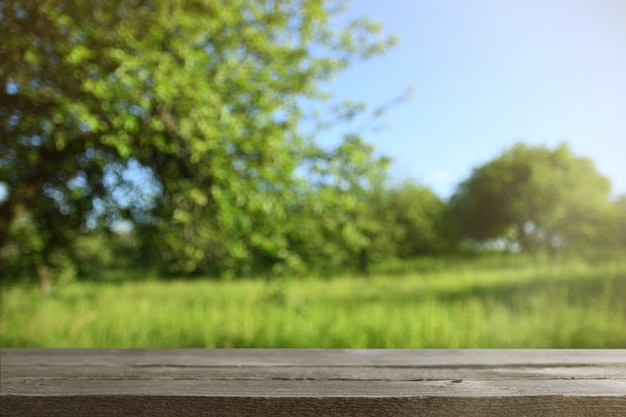 Bild des grauen holztischs vor zusammenfassung unscharfem natureof bäumen auf einer grünen wiese