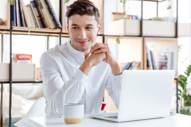 Bild des gutaussehenden mannes, der in weißem hemd gekleidet ist, kaffee trinkt und laptop-computer verwendet. coworking. blick in die kamera.