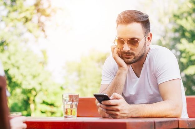 Bild des gutaussehenden mannes, der intelligentes telefon am freiencafé verwendet