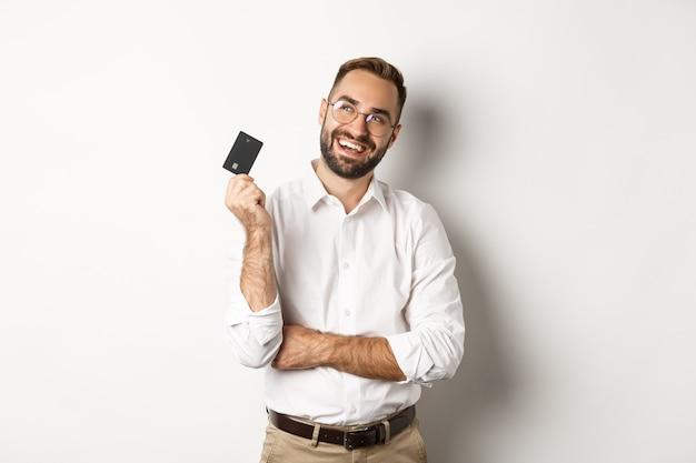 Bild des gutaussehenden mannes, der über das einkaufen und das halten der kreditkarte nachdenkt und nachdenklich den weißen hintergrund der oberen linken ecke betrachtet.
