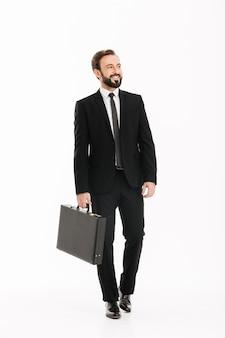 Bild des gutaussehenden mannes im geschäftsanzug in voller länge, der schwarze aktentasche trägt und beiseite schaut, lokalisiert über weißer wand