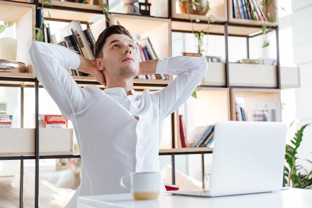 Bild des gutaussehenden mannes im weißen hemd gekleidet, das laptop-computer ausdehnt und verwendet. coworking. augen geschlossen.