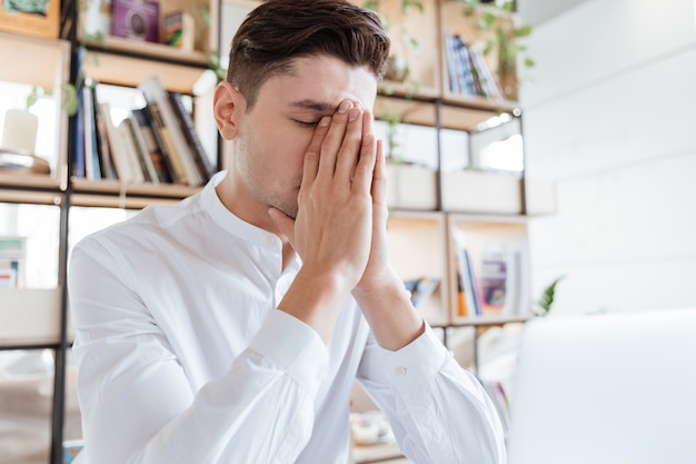 Bild des gutaussehenden mannes im weißen hemd mit laptop-computer gekleidet. coworking. augen geschlossen.