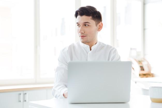Bild des gutaussehenden mannes im weißen hemd mit laptop-computer gekleidet. coworking. beiseite schauen.