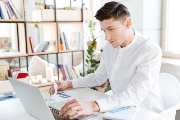 Bild des gutaussehenden mannes im weißen hemd mit laptop-computer gekleidet. coworking. computer betrachten.