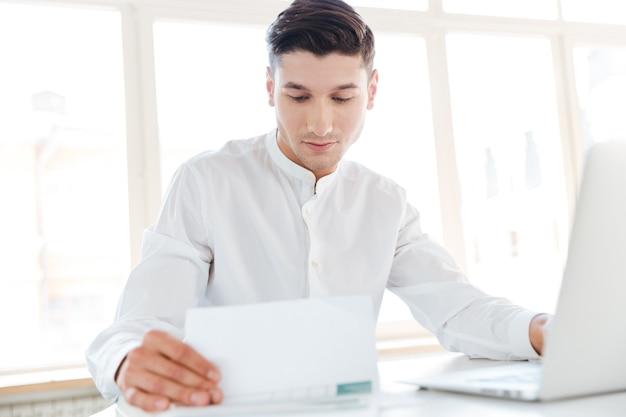 Bild des gutaussehenden mannes im weißen hemd mit laptop-computer gekleidet, während er dokumente hält. coworking. dokumente anschauen.