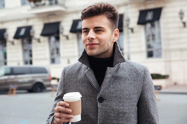 Bild des gutaussehenden mannes mitnehmerkaffee von der papierschale genießend, beim gehen hinunter leere straße