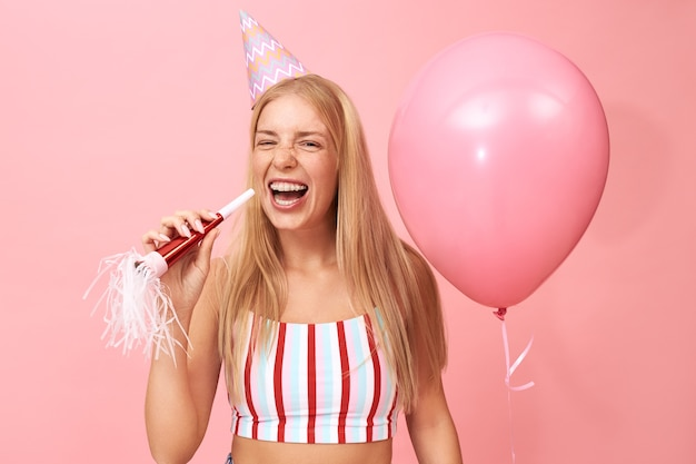 Bild des herrlichen niedlichen teenager-mädchens mit losen blonden haaren und zahnspangen, die auf rosa mit partygebläse und heliumballon aufwerfen, lachend mit weit geöffnetem mund