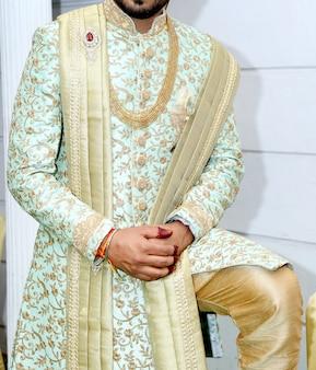 Bild des hübschen bräutigams kleidete in der reichen ethnischen indischen art für eine hochzeit an