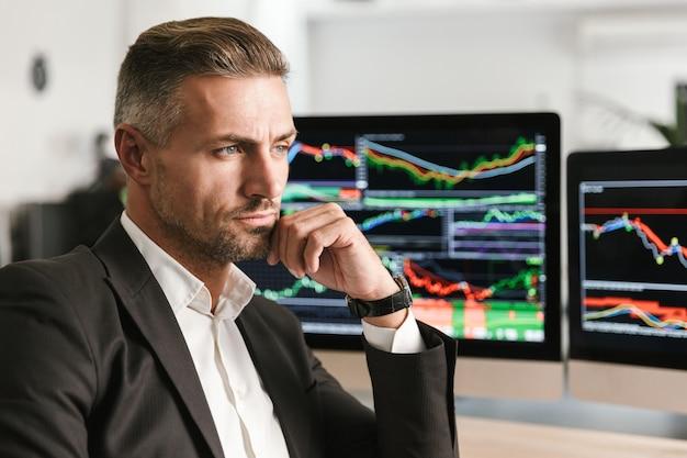 Bild des hübschen geschäftsmanns 30s, der anzug trägt, der im büro am computer mit grafiken und diagrammen am bildschirm arbeitet