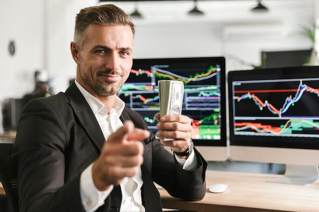 Bild des hübschen geschäftsmanns der 30er jahre, der anzug hält packung des geldes während der arbeit im büro mit grafiken und diagrammen auf computer hält