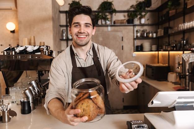 Bild des hübschen glücklichen kaffeemannes, der in der cafébar aufwirft, die drinnen arbeitet und kekse hält.